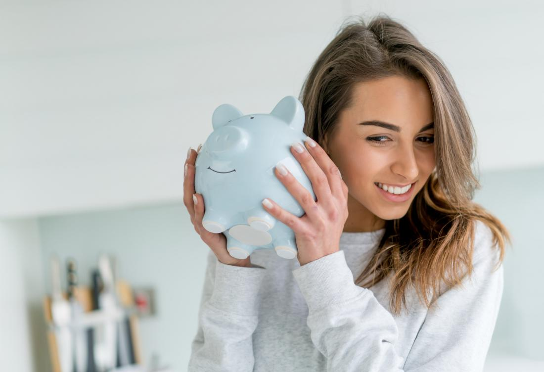 woman shaking piggy bank