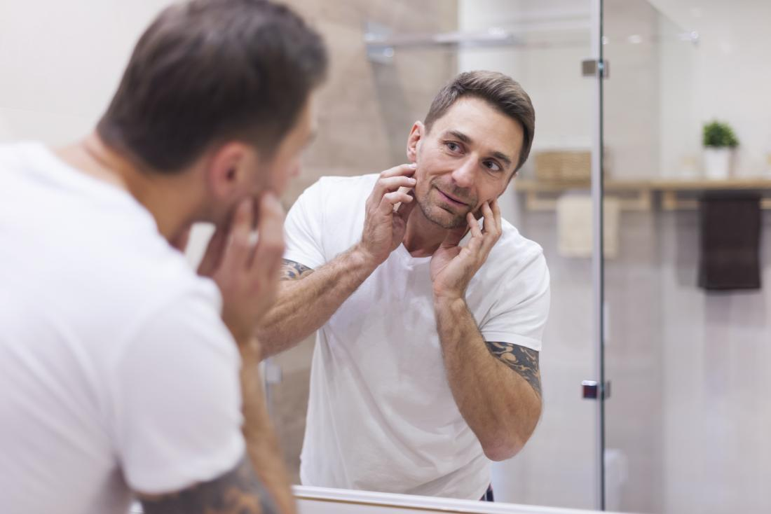 man checking his skin in mirror