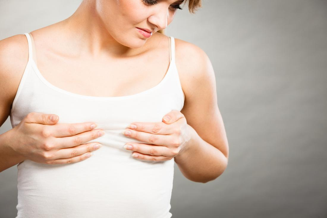 Woman holding her breasts because of nipple pain.
