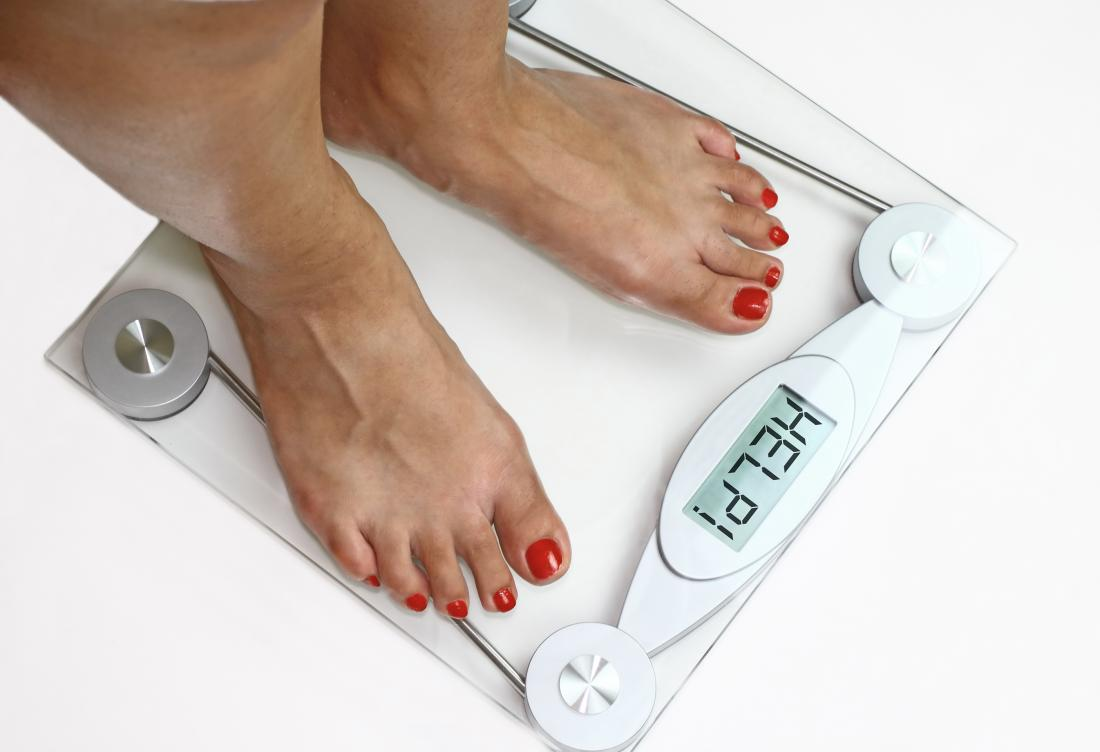 a woman weighing herself on a set of scales