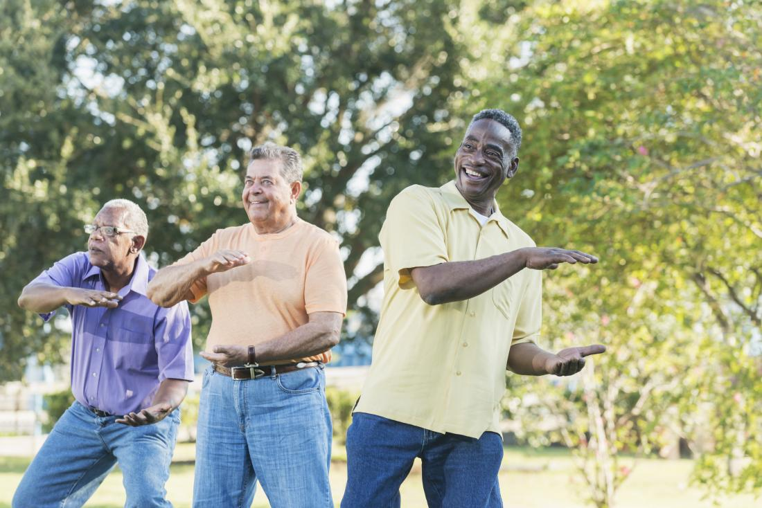 three senior men doing tai chi outdoors.