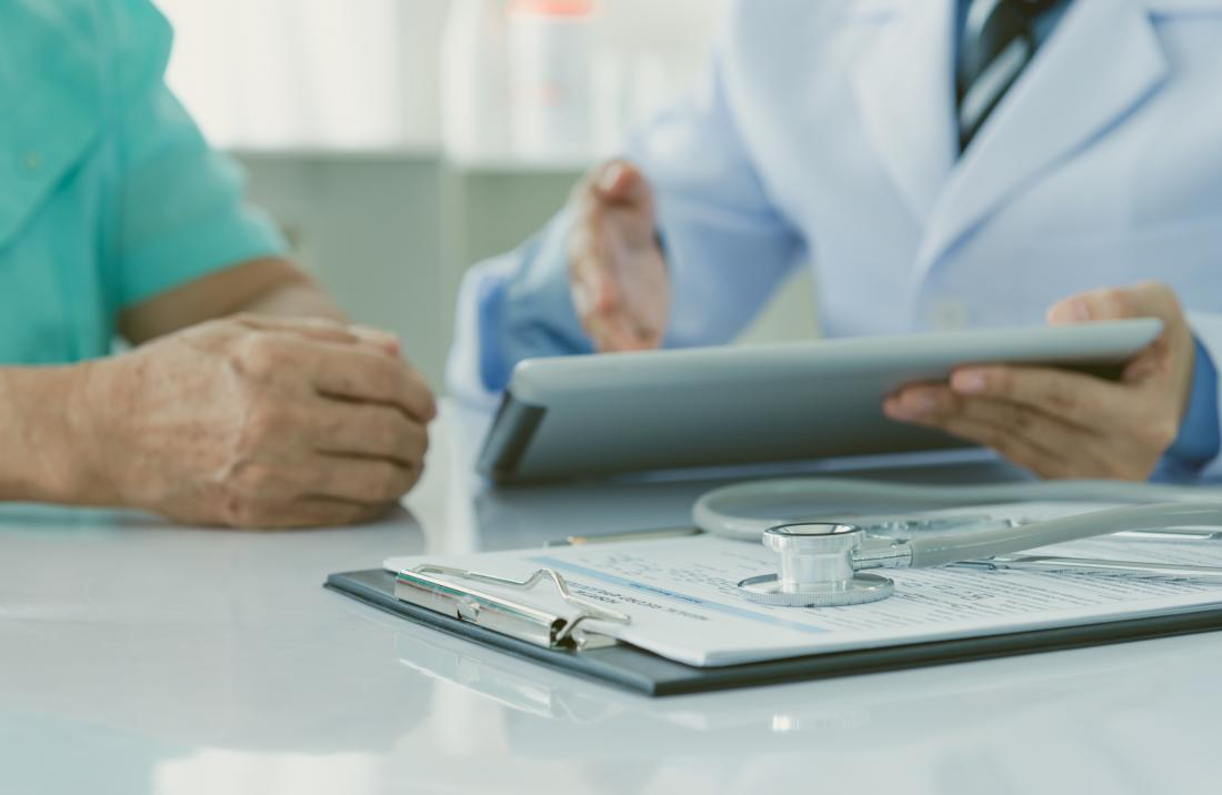 Doctor discussing results with patient, with clipboard and stethoscope in foreground.