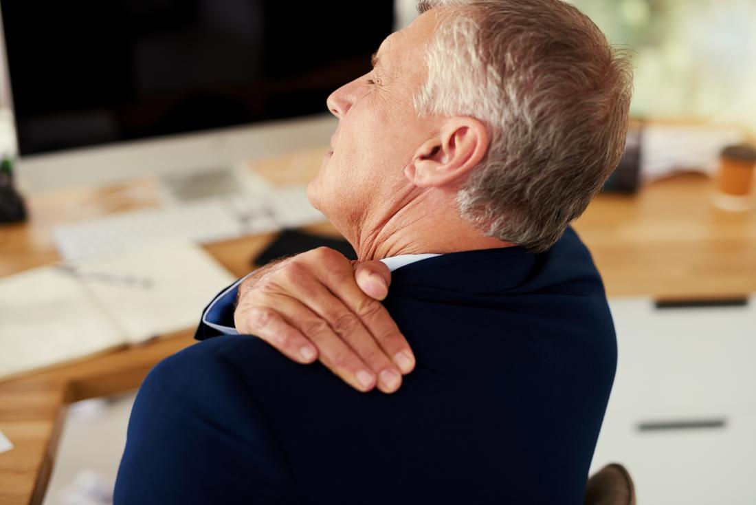Businessman with shoulder bursitis holding top of shoulder and back in pain, sitting at desk at work.