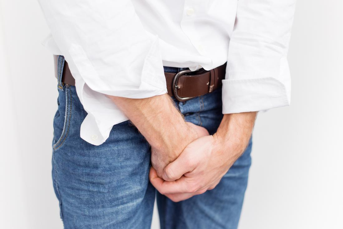 Man in jeans covering an unwanted erection with his hands over his crotch area
