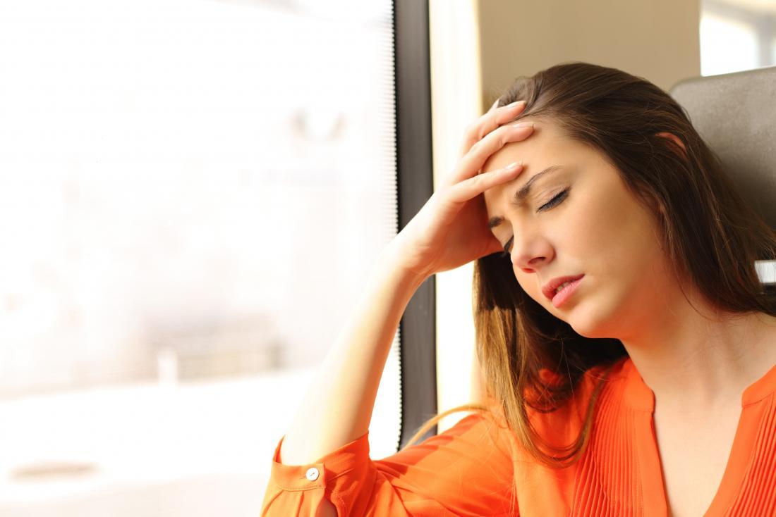 Dizzy woman on train experiencing headache and fatigue.