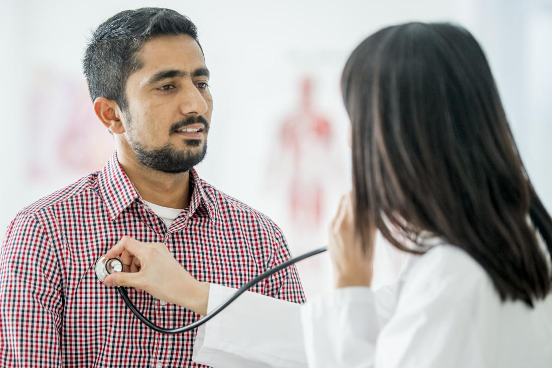 Doctor using stethoscope to listen to patients breathing.