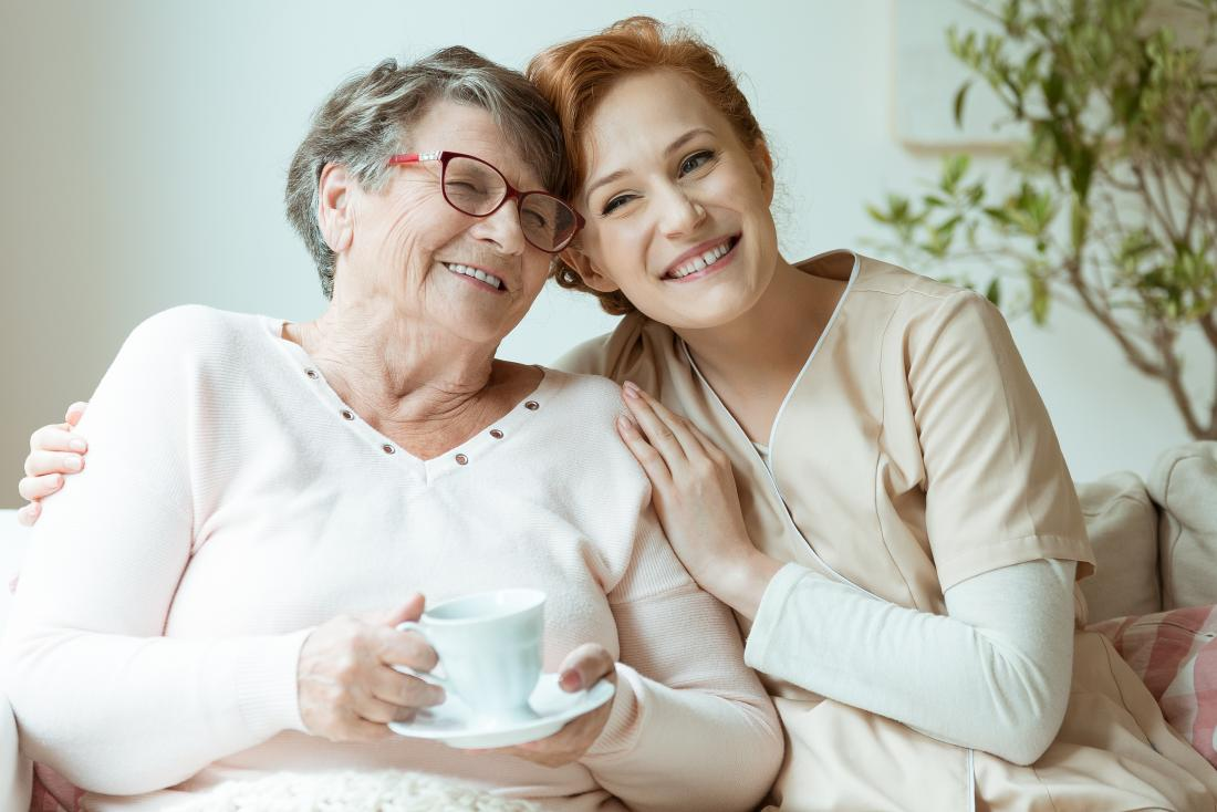 senior woman drinking coffee with younger nurse