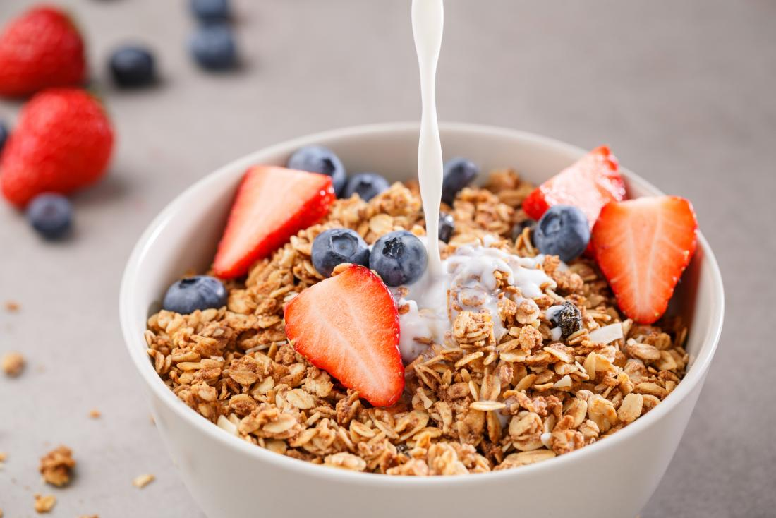 Bowl of fortified granola or muesli cereal with strawberries and blueberries, with soya plant milk being poured on top.