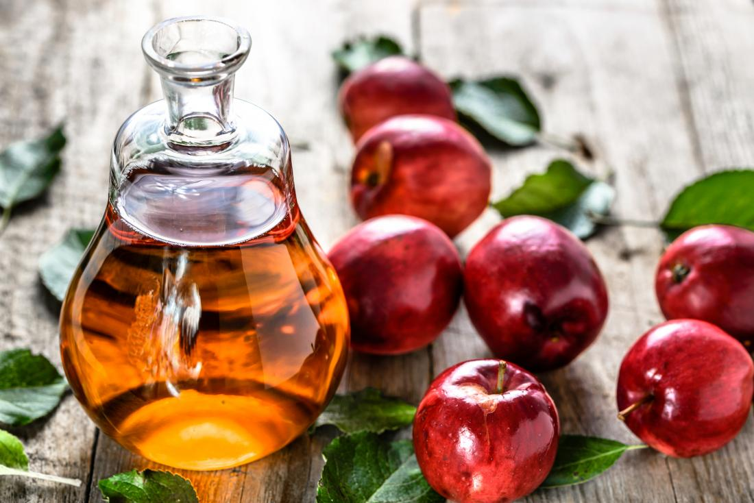 Apple cider vinegar in glass bottle on table with red apples.