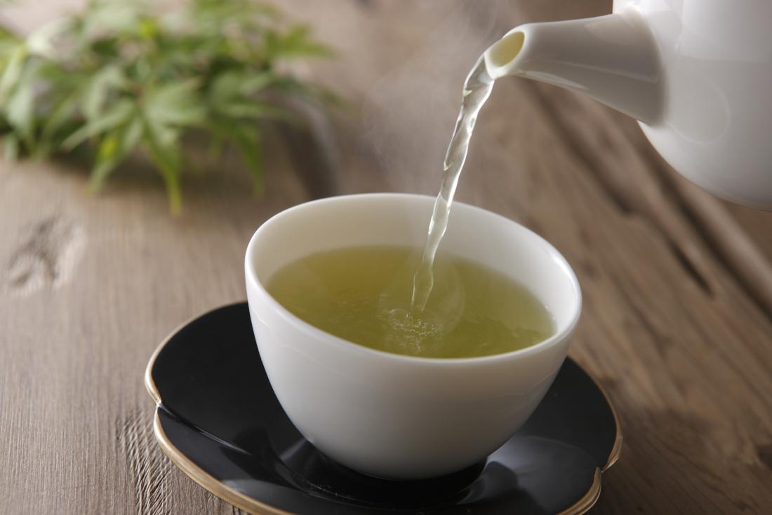 Herbal green tea being poured from teapot into cup.
