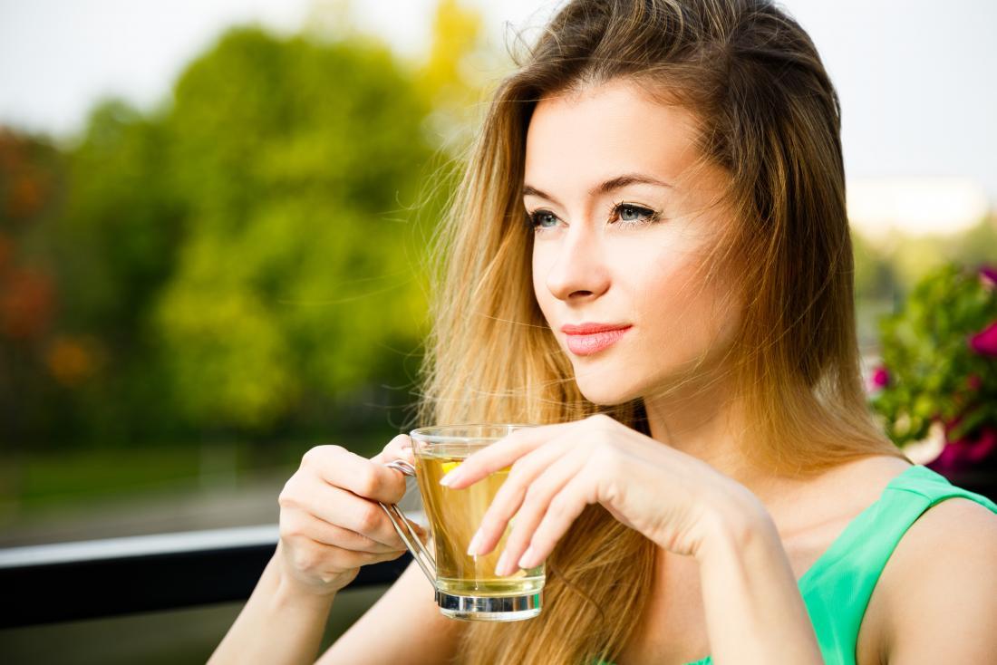 Woman outside drinking green herbal tea.