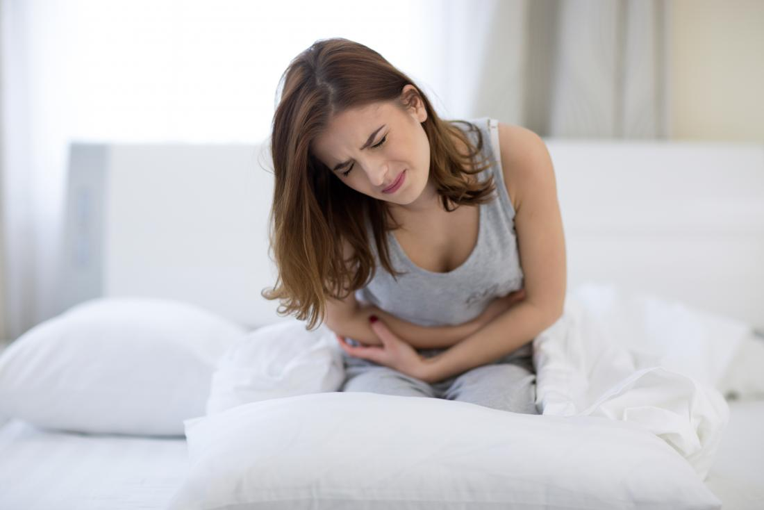 Woman clutching stomach in pain because of IBS.