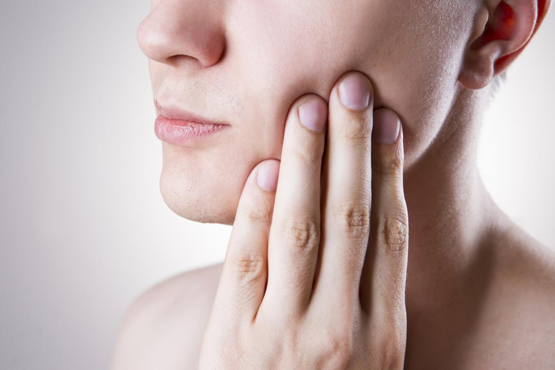 Woman with pericoronitis rubbing cheek ache from wisdom tooth.