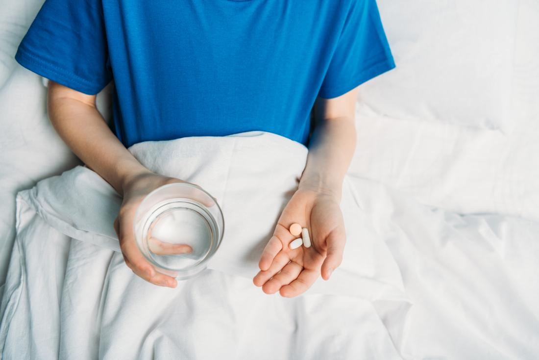 Child taking pills in bed