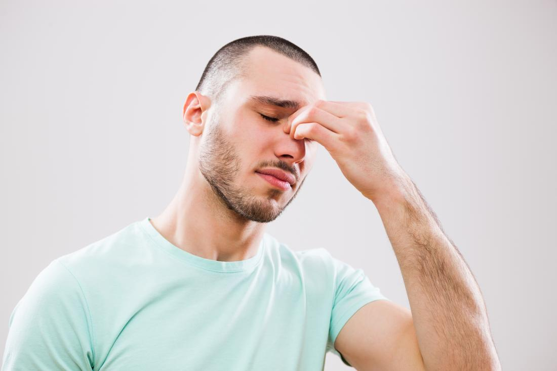 Man with headache and sinusitis holding sinus in pain.