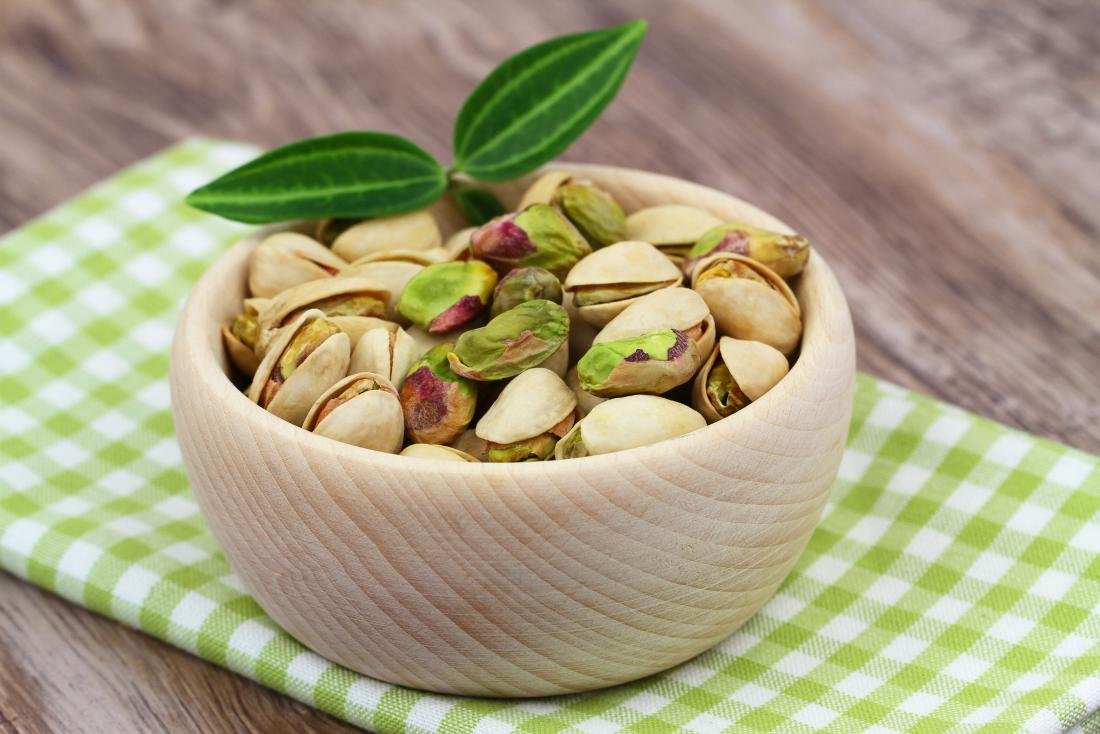 A bowl of pistachios on a cloth