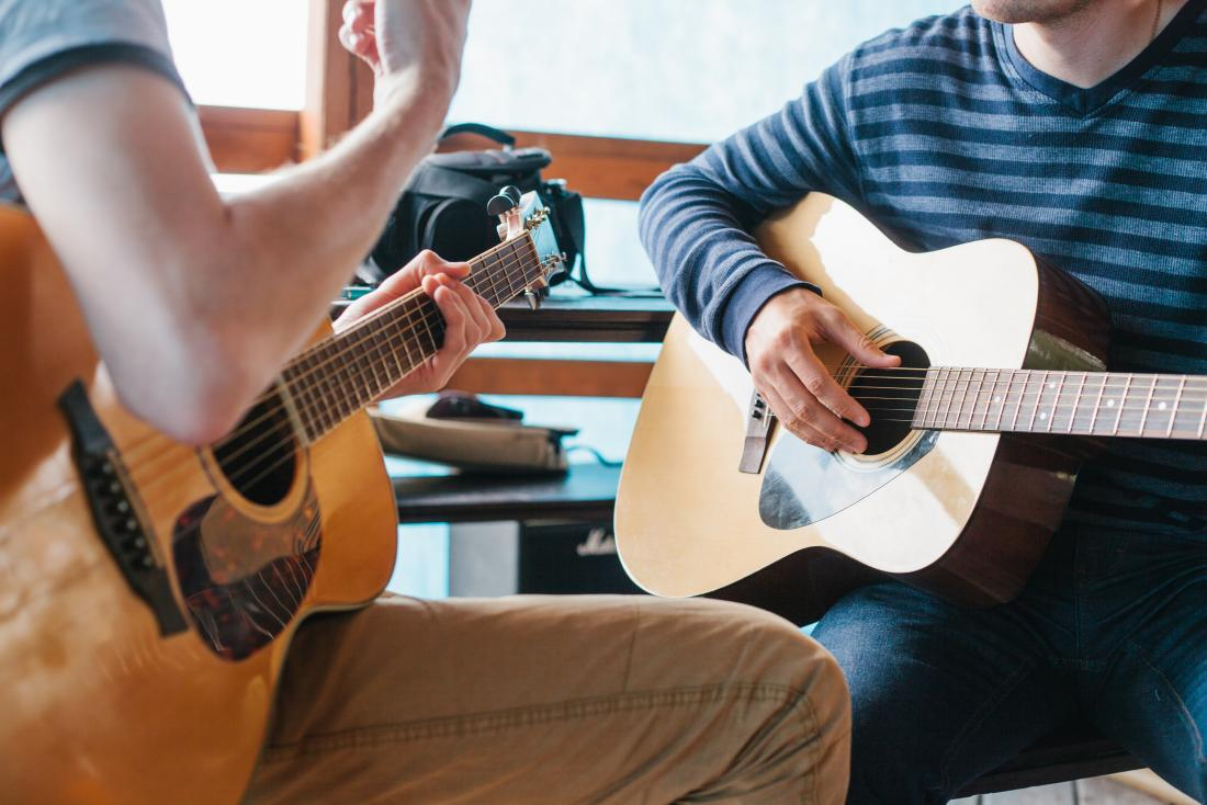 two people playing guitars