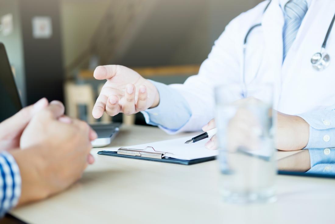 Médecin et patient en consultation sur le traitement de la maladie.