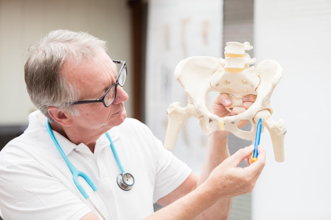 Doctor explaining iliopsoas bursitis by pointing to hip joint on anatomical model.