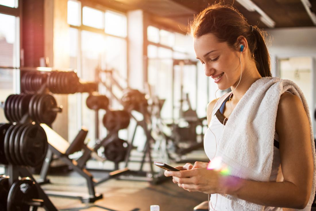 woman looking at phone in gym