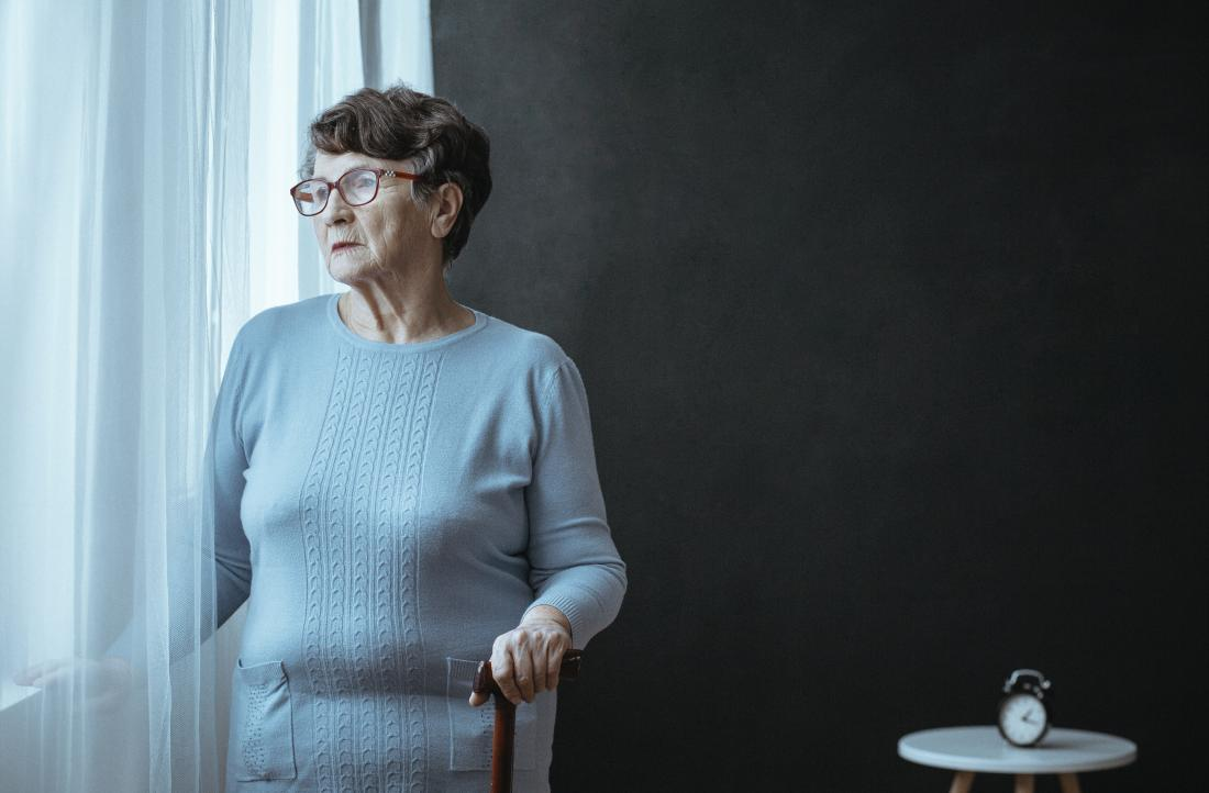 older lady with parkinsonsism looking out of a window