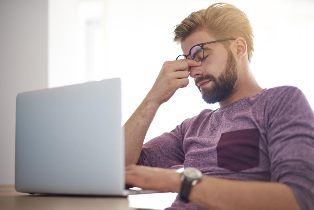피곤 된 눈으로 컴퓨터에 앉아 남자