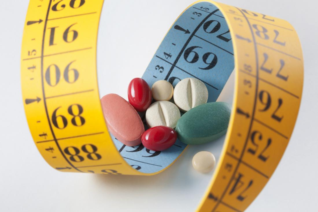 Weight loss and diet pills surrounded by measuring tape.