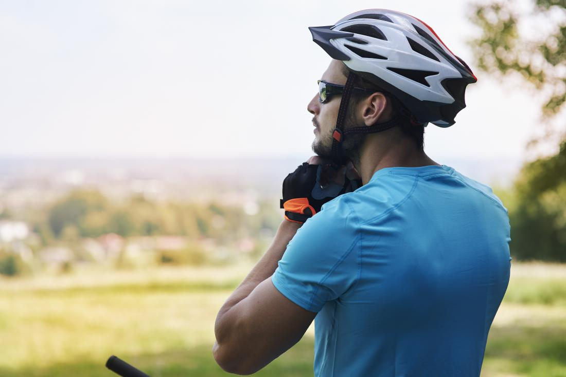 Man wearing cycling helmet outdoors.