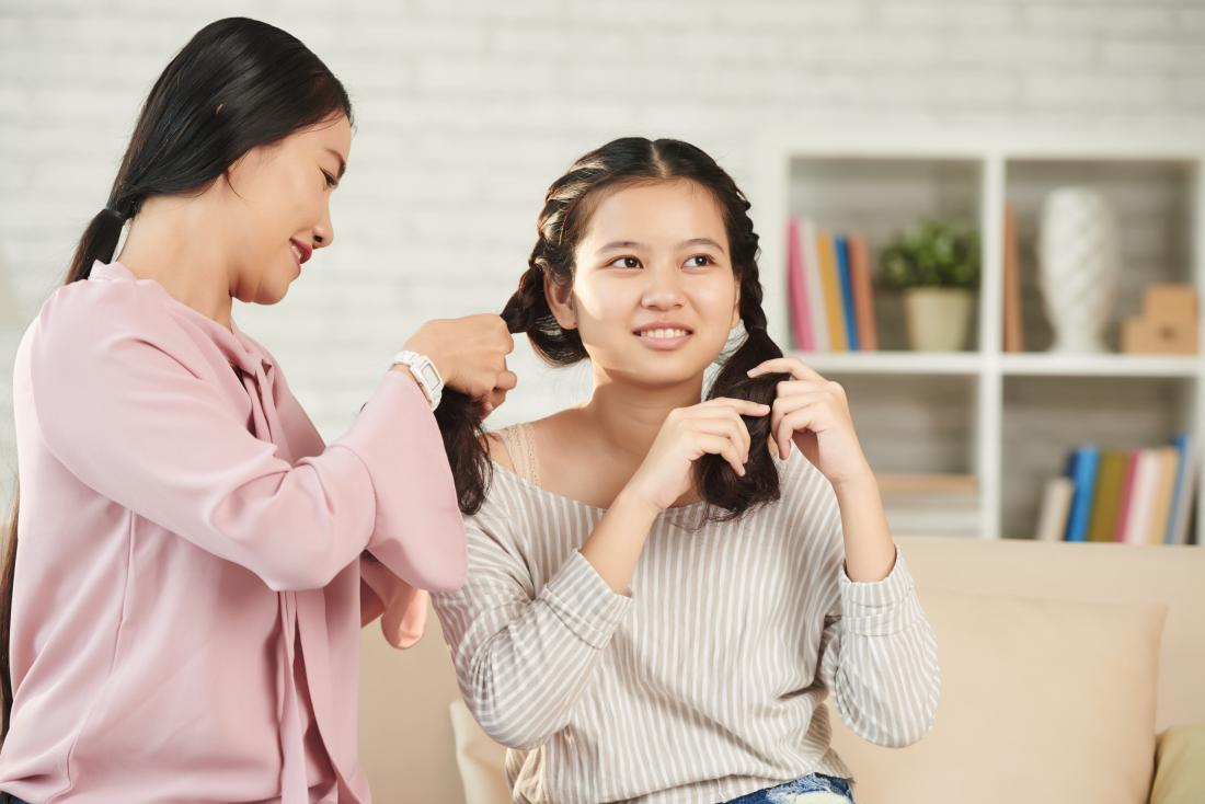 Women braiding hair and testing out different hairstyles.