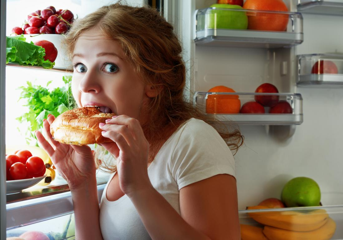 a woman snacking from the fridge