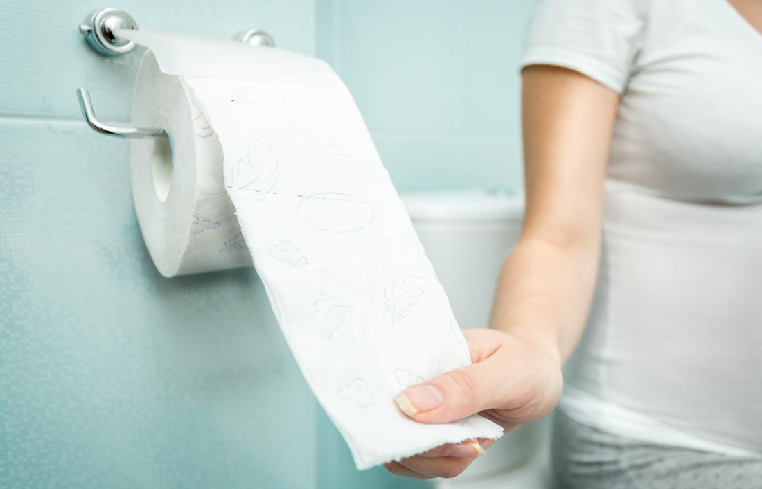 woman reaching for toilet paper because of sticky poop.