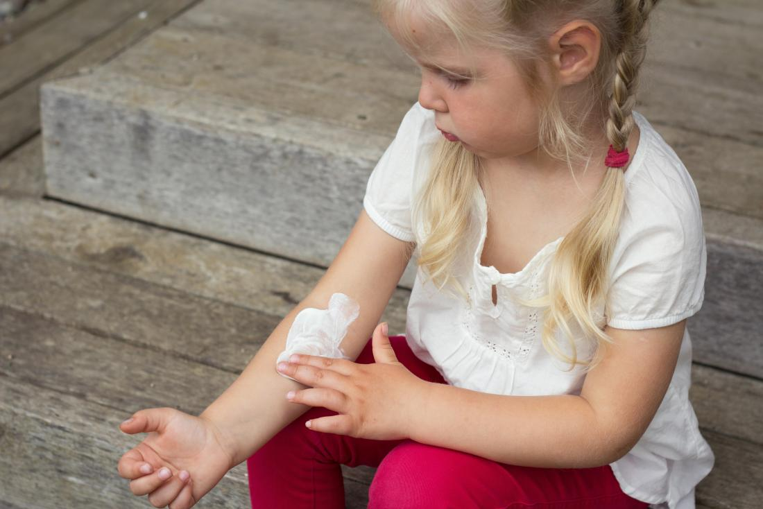 little girl putting cream on her arm