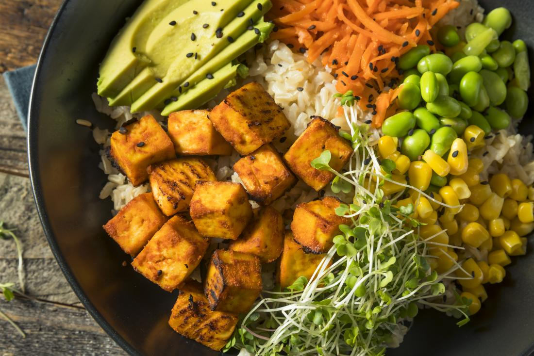 Healthy and nutritious plant based meal for the hepatitis C diet, including tofu, brown rice, beans, avocado, carrot, watercress, and sweetcorn.