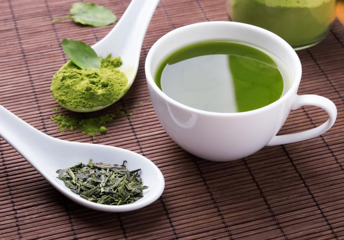 Herbal supplements in the form of matcha powder and loose leaf tea on spoons, next to cup of green tea.