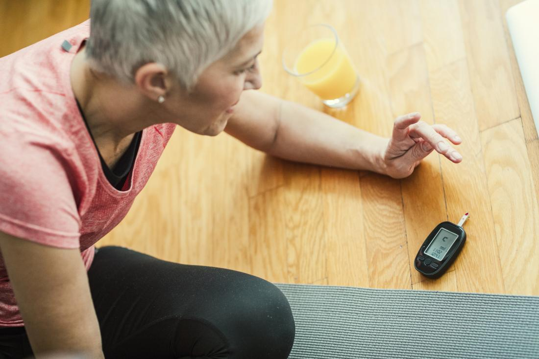 Woman checking blood sugar levels after exercising next to glass of orange juice.