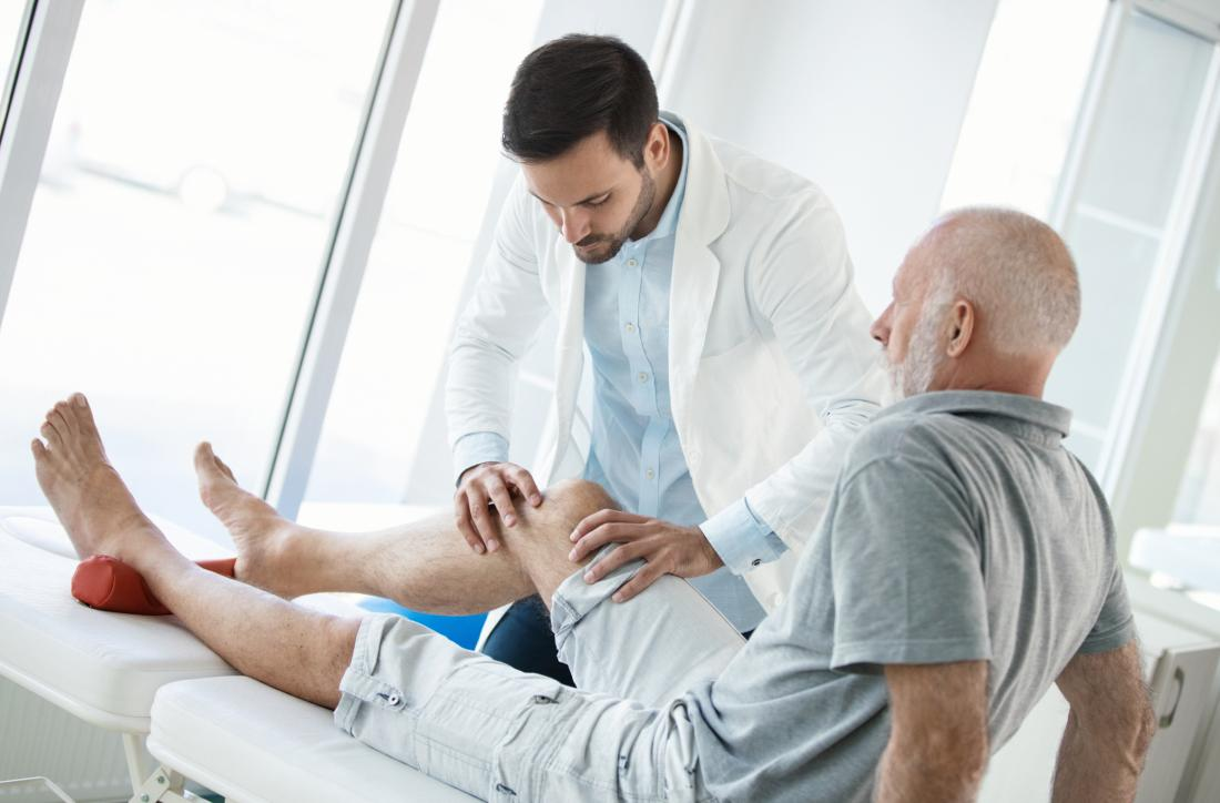 Senior man with iliotibial band syndrome having his knee inspected by doctor during physical therapy.