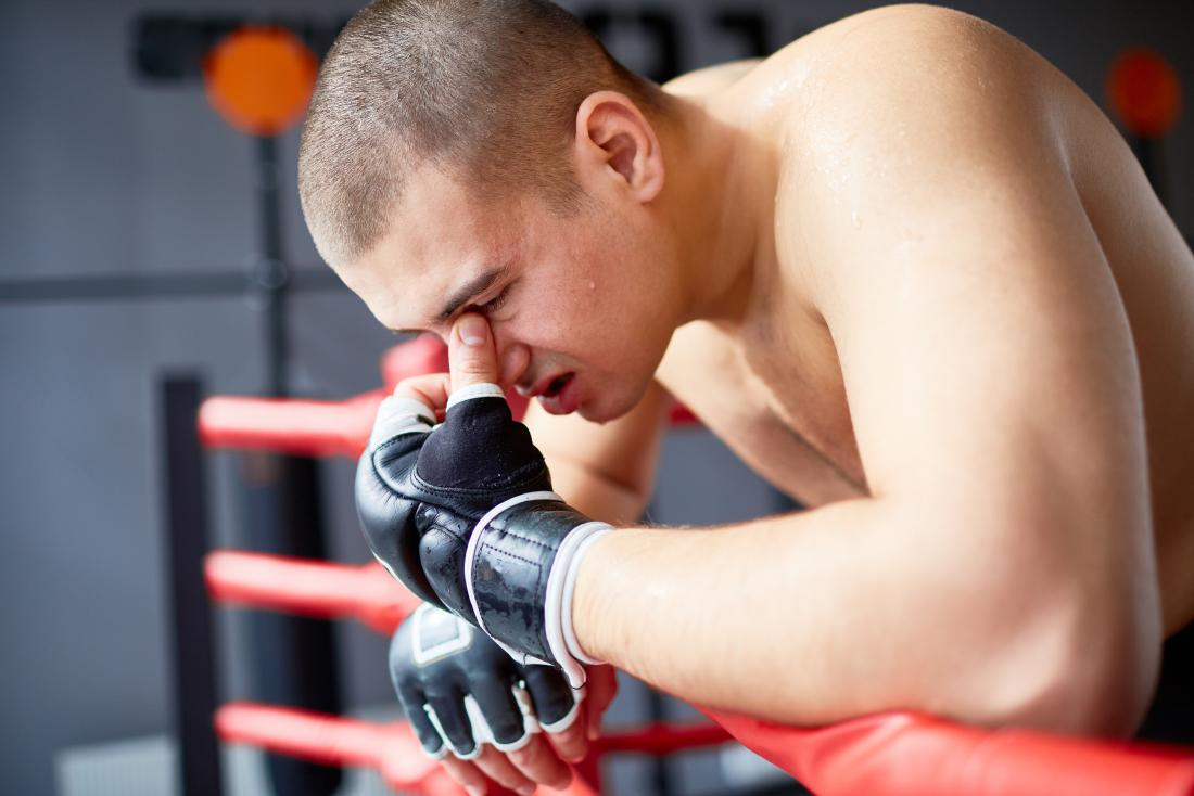 Boxer or fighter leaning on ring holding bridge of nose because of injury causing headache pain.