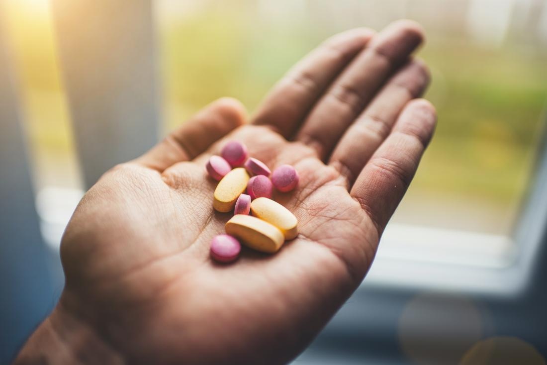 Person holding a number of medication pills and supplement vitamins in palm of hand.
