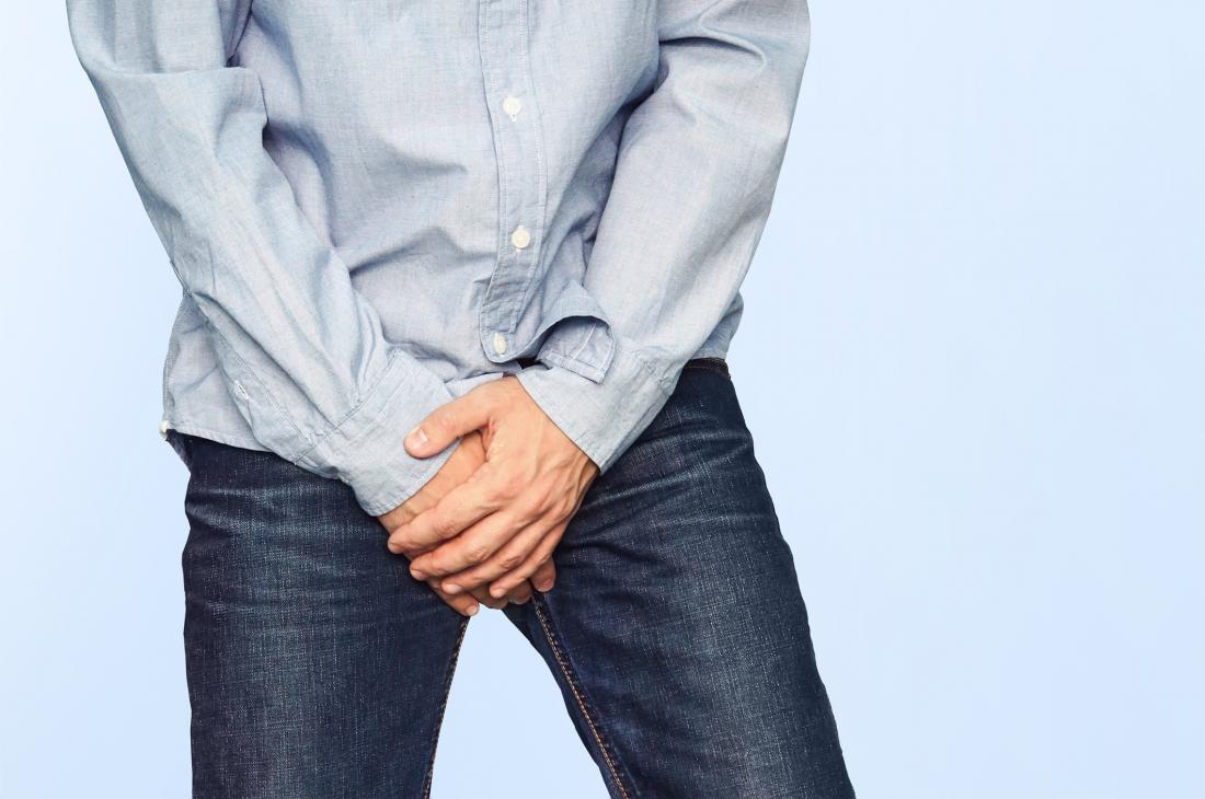 Man in jeans with scrotal eczema covering his crotch with his hands.