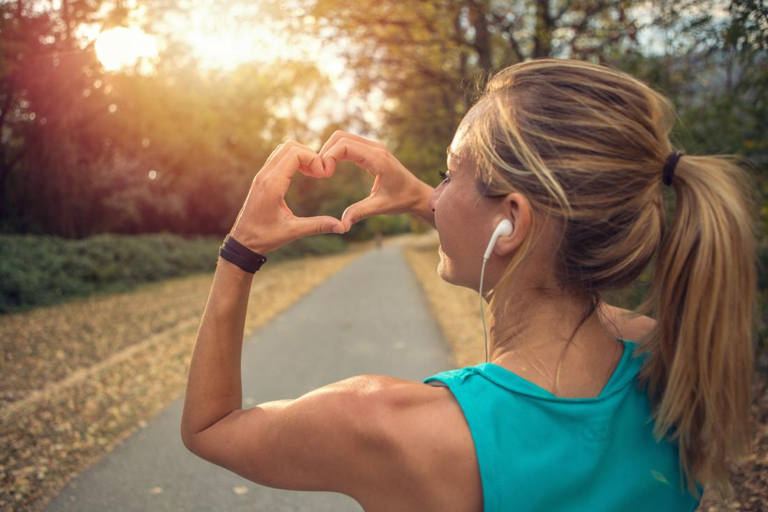 Woman improving circulation outside jogging and running through park making heart symbol with her hands.