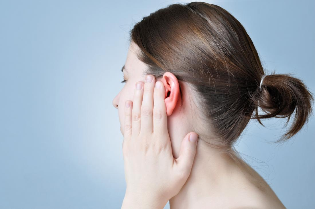 Woman covering her ear in pain.