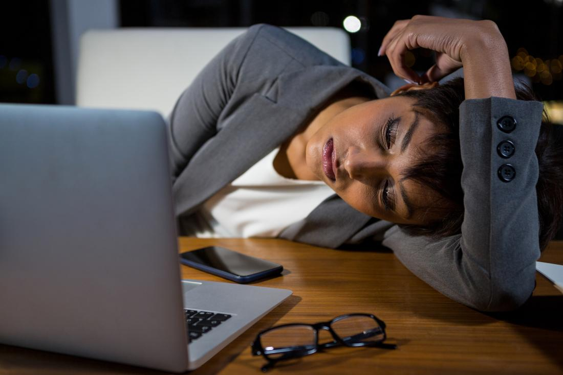 a woman falling asleep at her desk