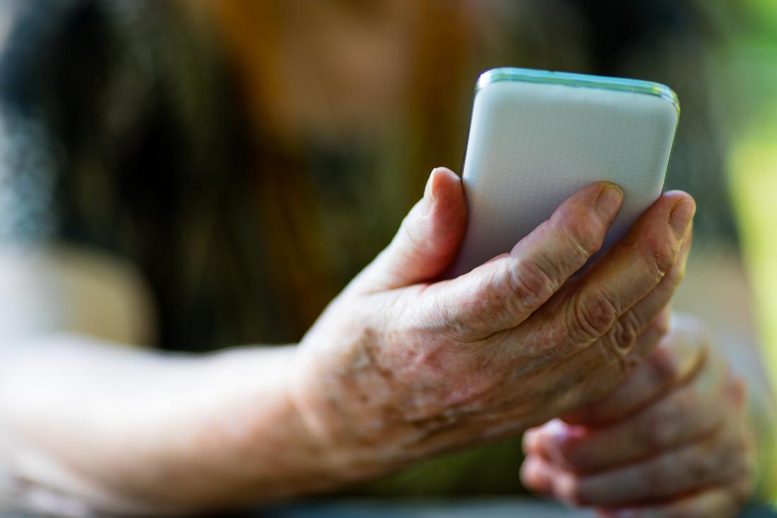 older person holding phone