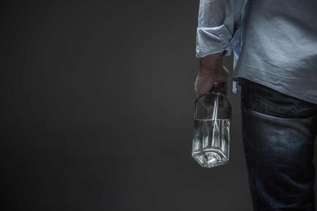 man clenching bottle of alcohol seen from behind