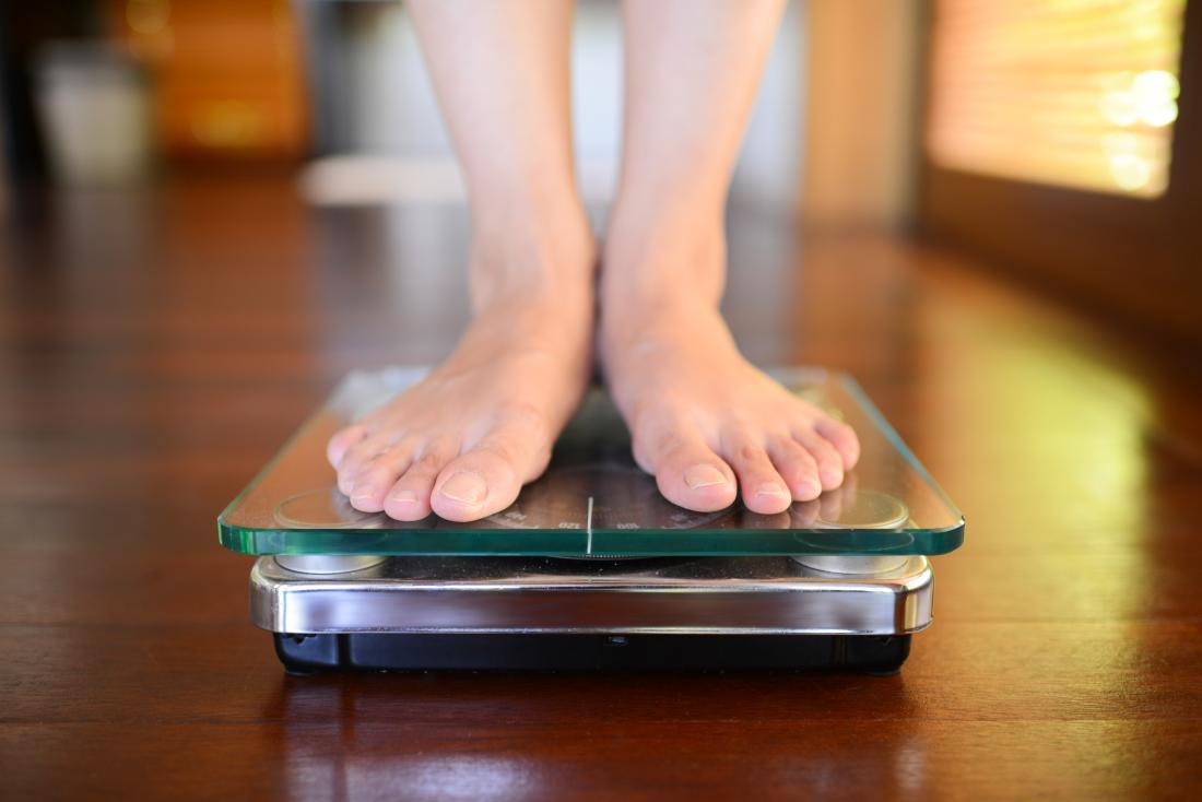 Man standing on weighing scales representing average weight for men.