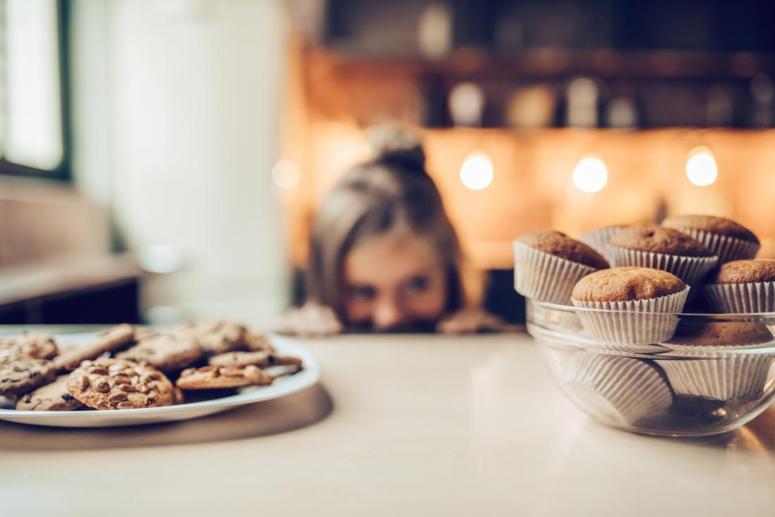 Child in a kitchen eyeing up cookies