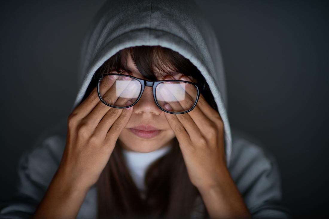 Woman with pressure behind her eyes rubbing eyes under glasses.
