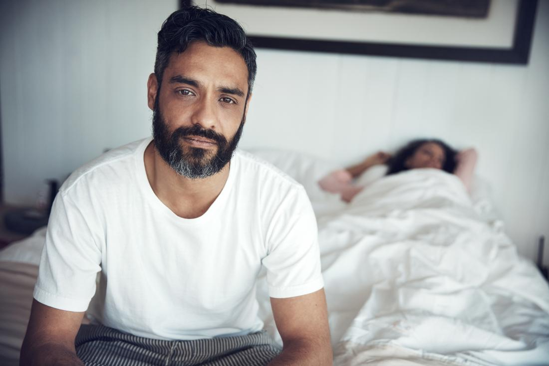 Man with enlarged prostate wondering how it will effect his sex life sitting on end of bed while woman sleeps.