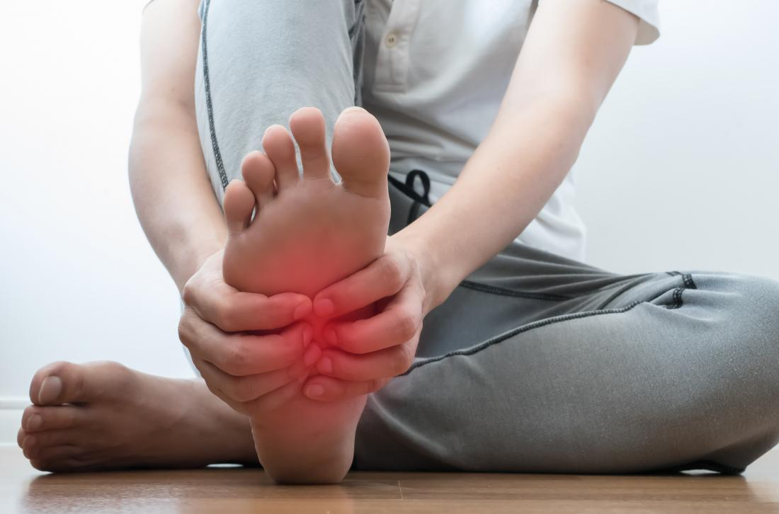 Man holding his foot with possible broken foot symptoms