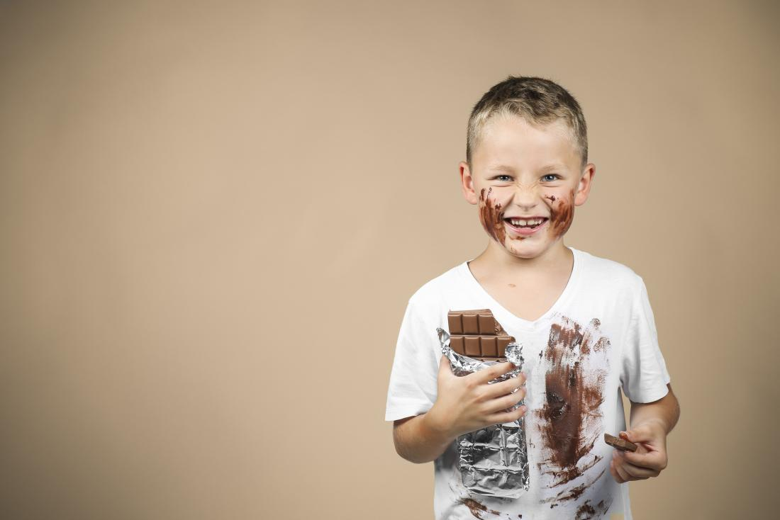 Happy boy eating chocolate